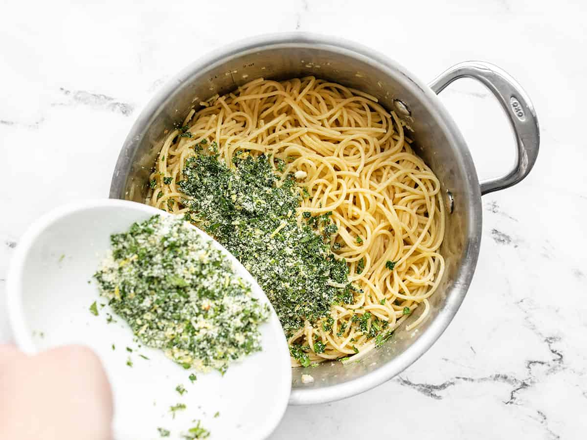 parsley and parmesan mixture being poured into the pot