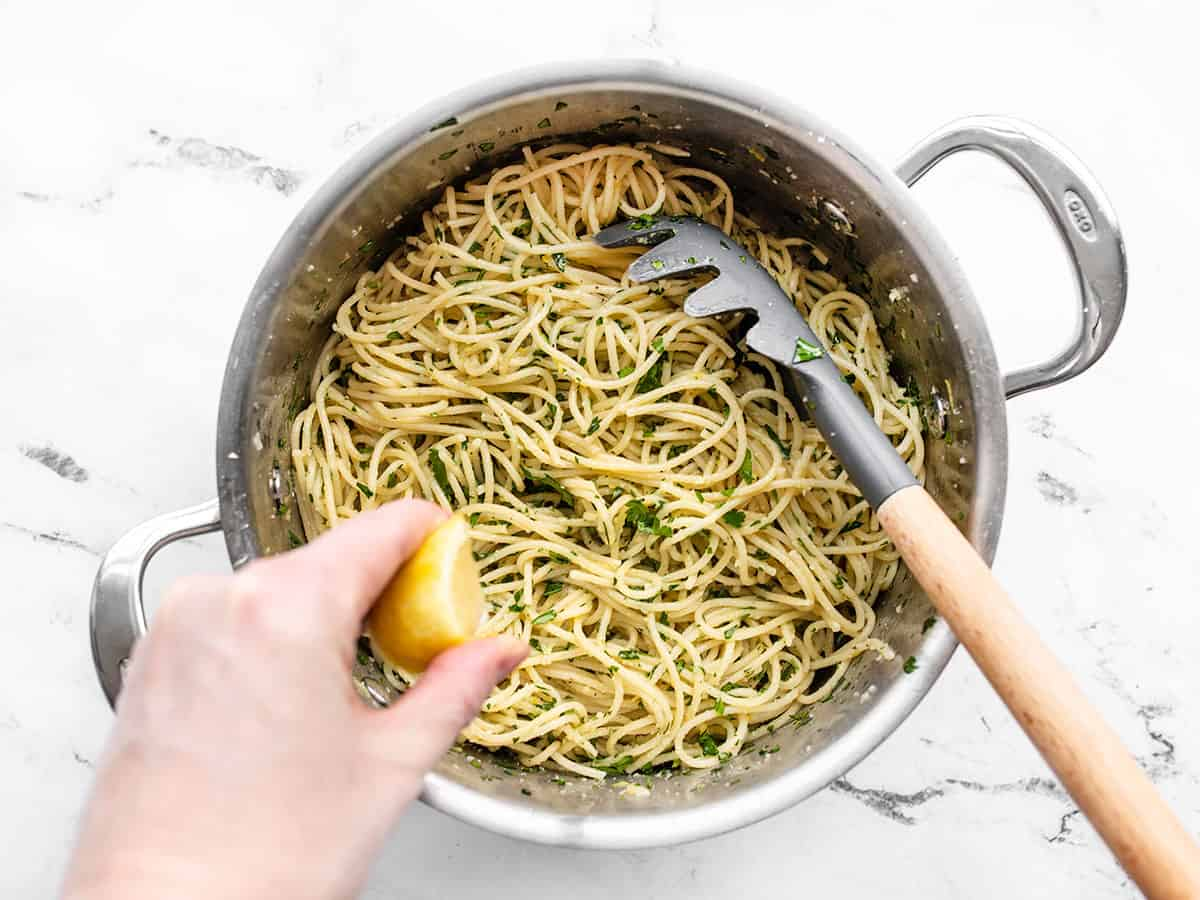 Lemon being squeezed into the pasta in the pot