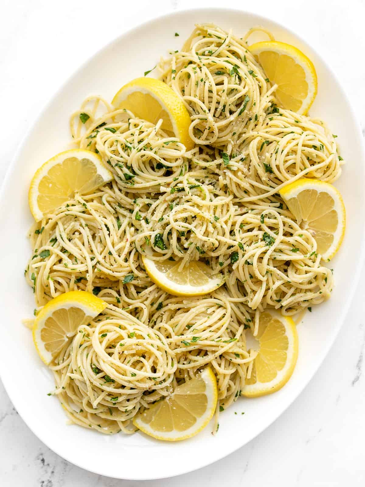 Overhead view of an oval platter full of lemon parsley pasta with lemon slices as garnish