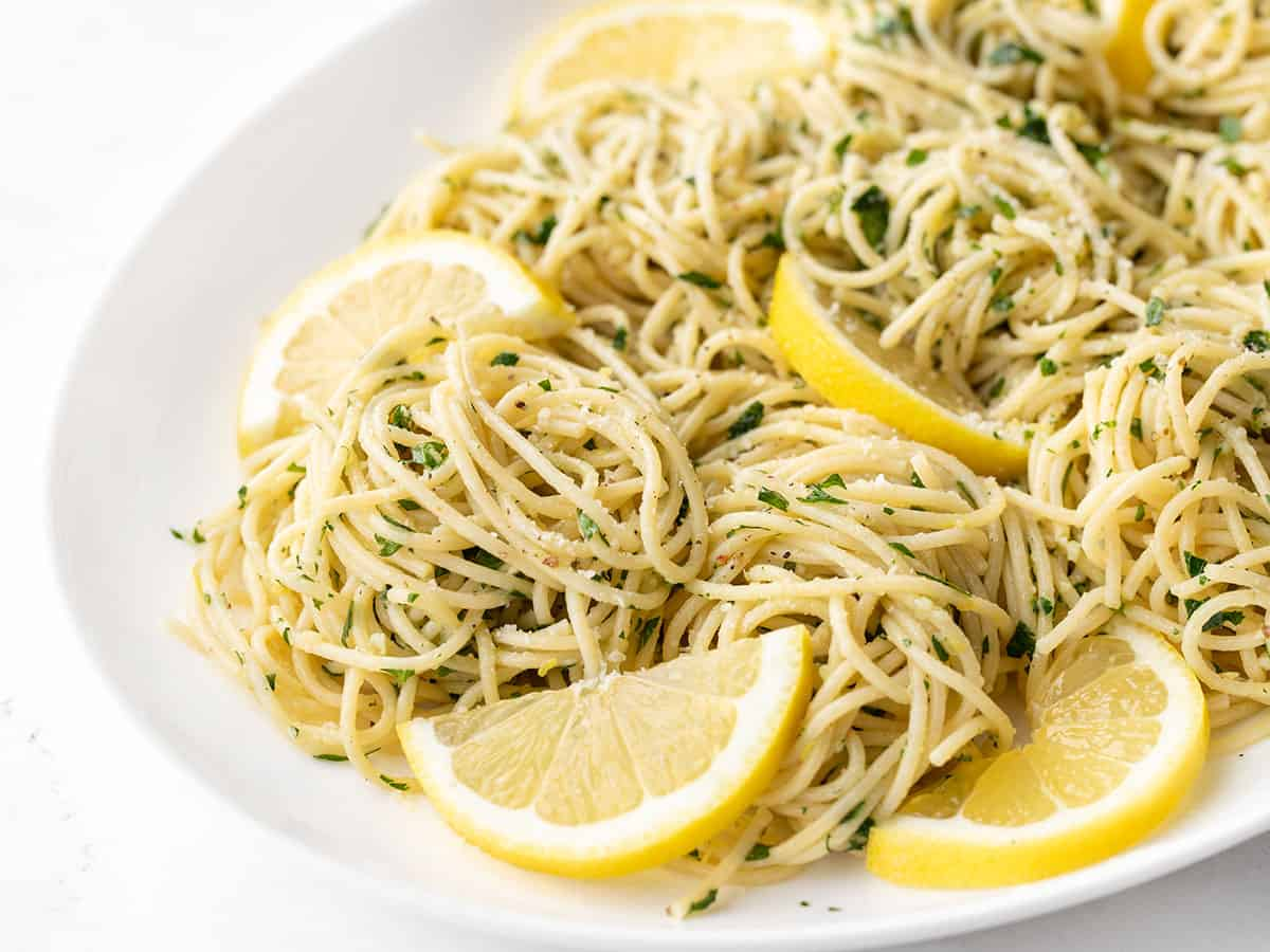 Close up side view of lemon parsley pasta on a platter with lemon slices