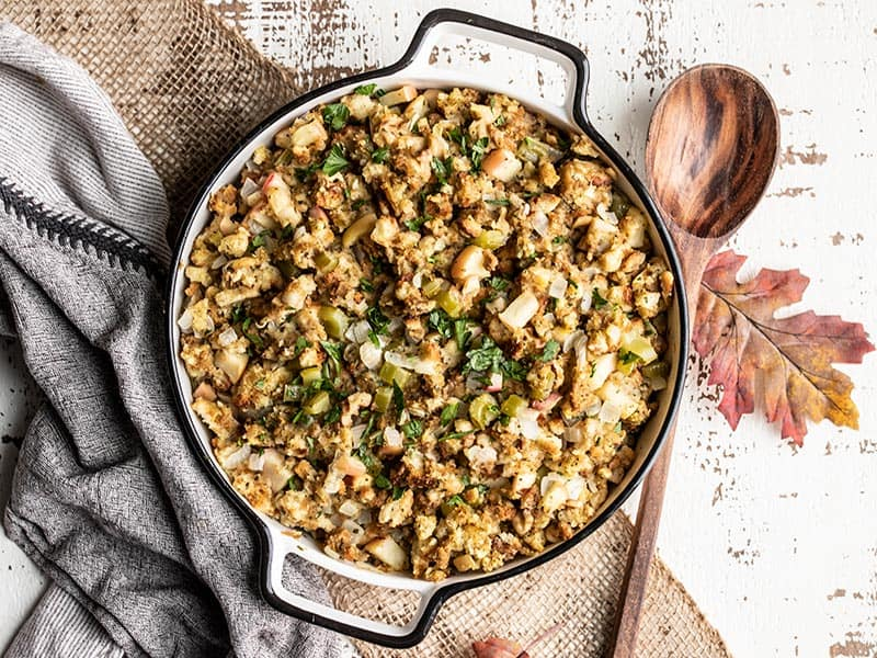 A casserole dish full of the finished Apple Walnut Stuffing, garnished with chopped parsley