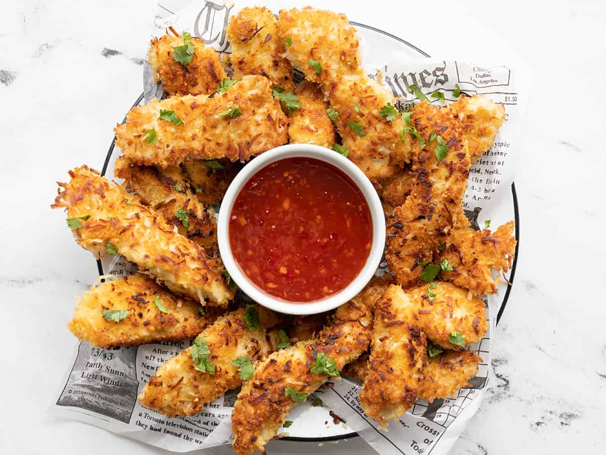 Overhead view of a plate full of coconut chicken strips with a bowl of sweet chili sauce in the center