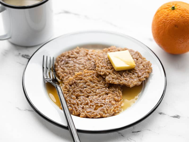 Front view of rice pancakes on a plate with butter and maple syrup, an orange and cup of coffee in the back