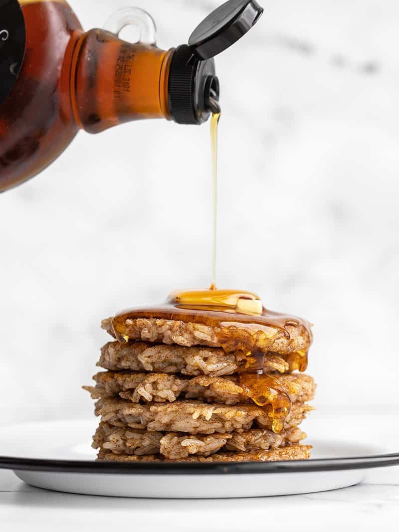Side view of a stack of rice pancakes with butter and syrup being poured over top