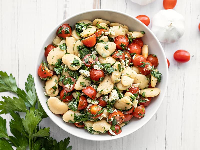 Overhead view of a bowl full of Mediterranean White Bean Salad with parsley, tomatoes, and garlic on the side