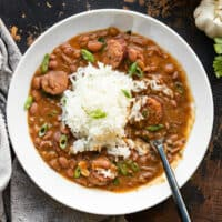 A bowl full of red beans and rice with sausage, a spoon in the center of the bowl