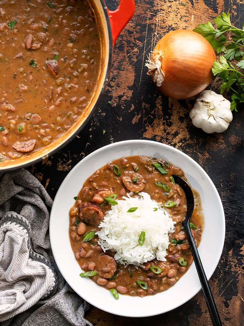 A serving of red beans and rice next to the pot full of red beans.