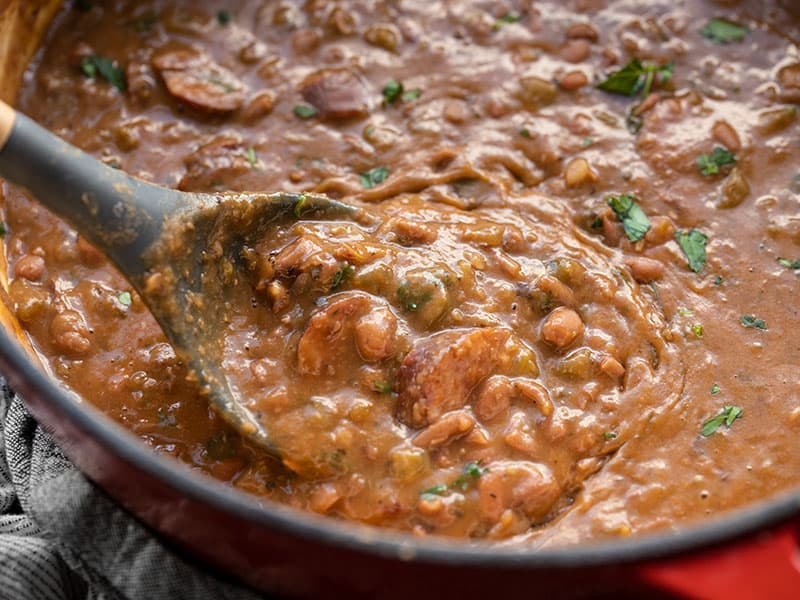 Close up of a spoon scooping some red beans and andouille sausage out of the pot