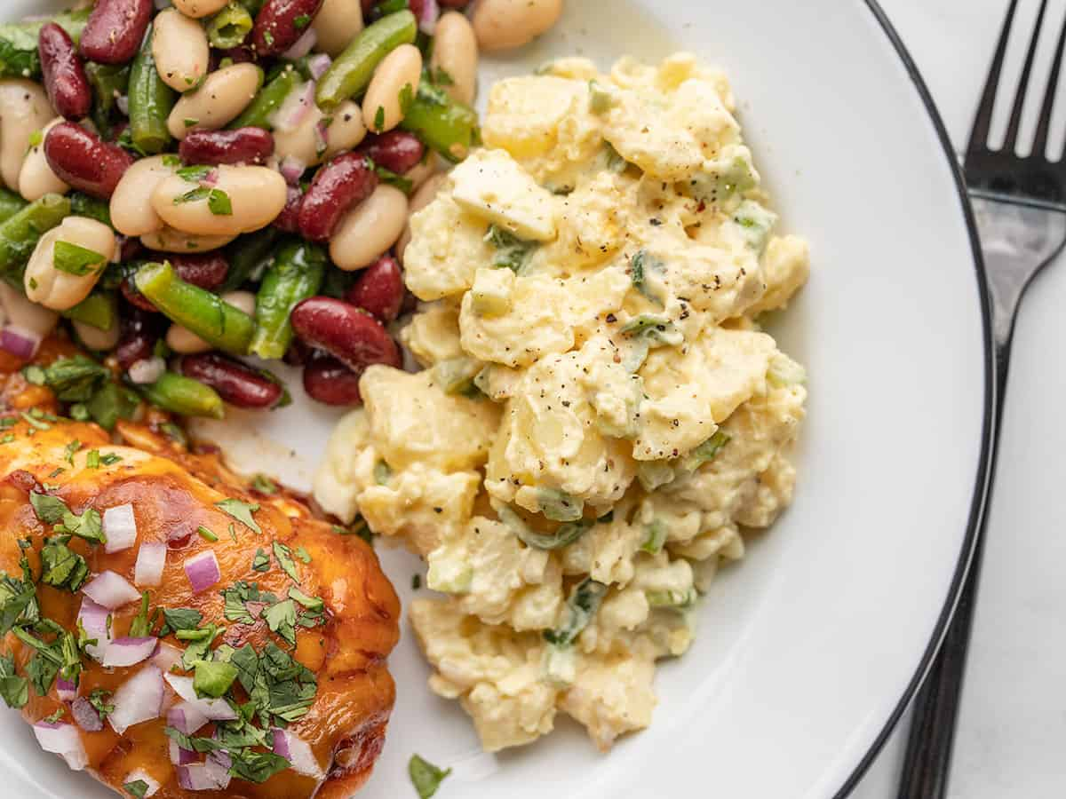 potato salad on a plate with bbq chicken and three bean salad