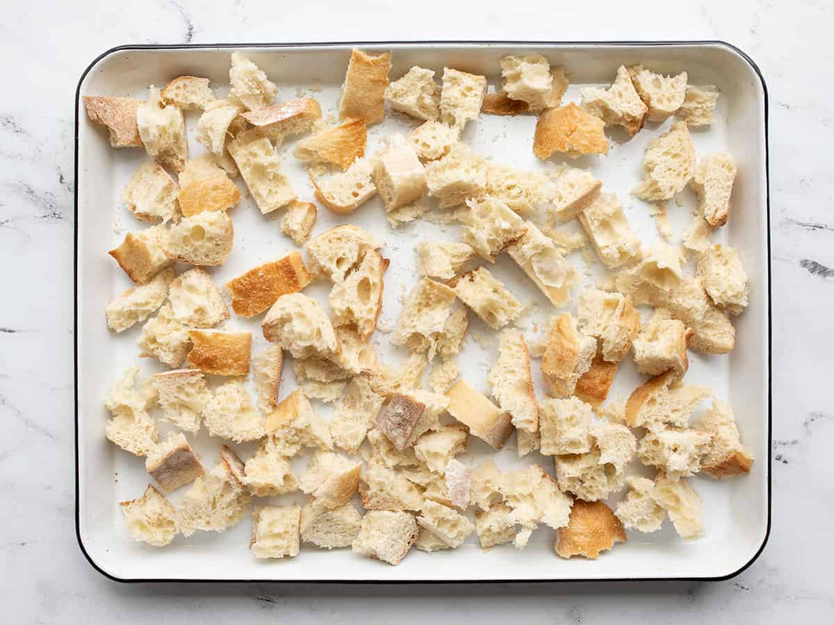 Torn bread pieces on a baking sheet