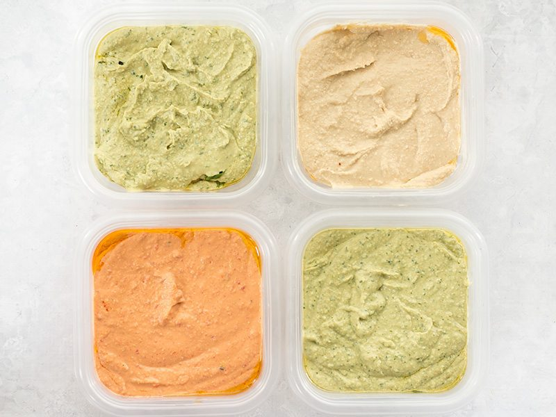 Four flavors of homemade hummus in containers ready for the refrigerator