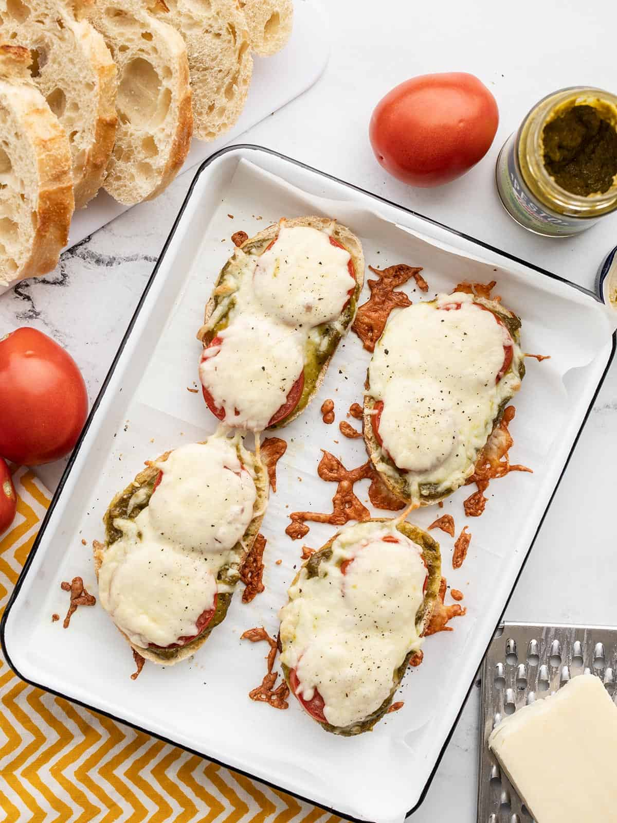Pesto cheese toast on a baking sheet with bread, tomatoes and cheese on the sides