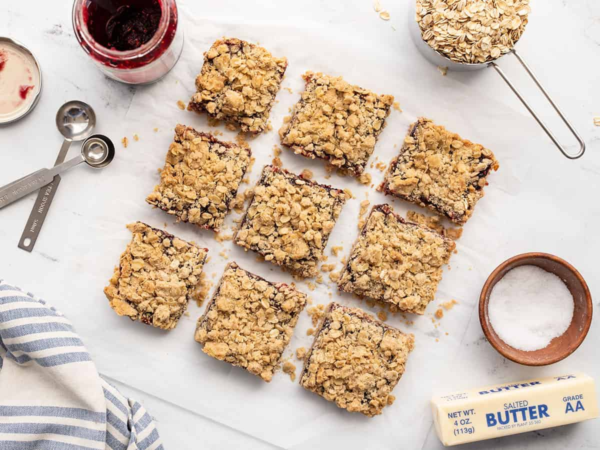 Overhead view of raspberry oatmeal bars cut into squares with ingredients on the sides