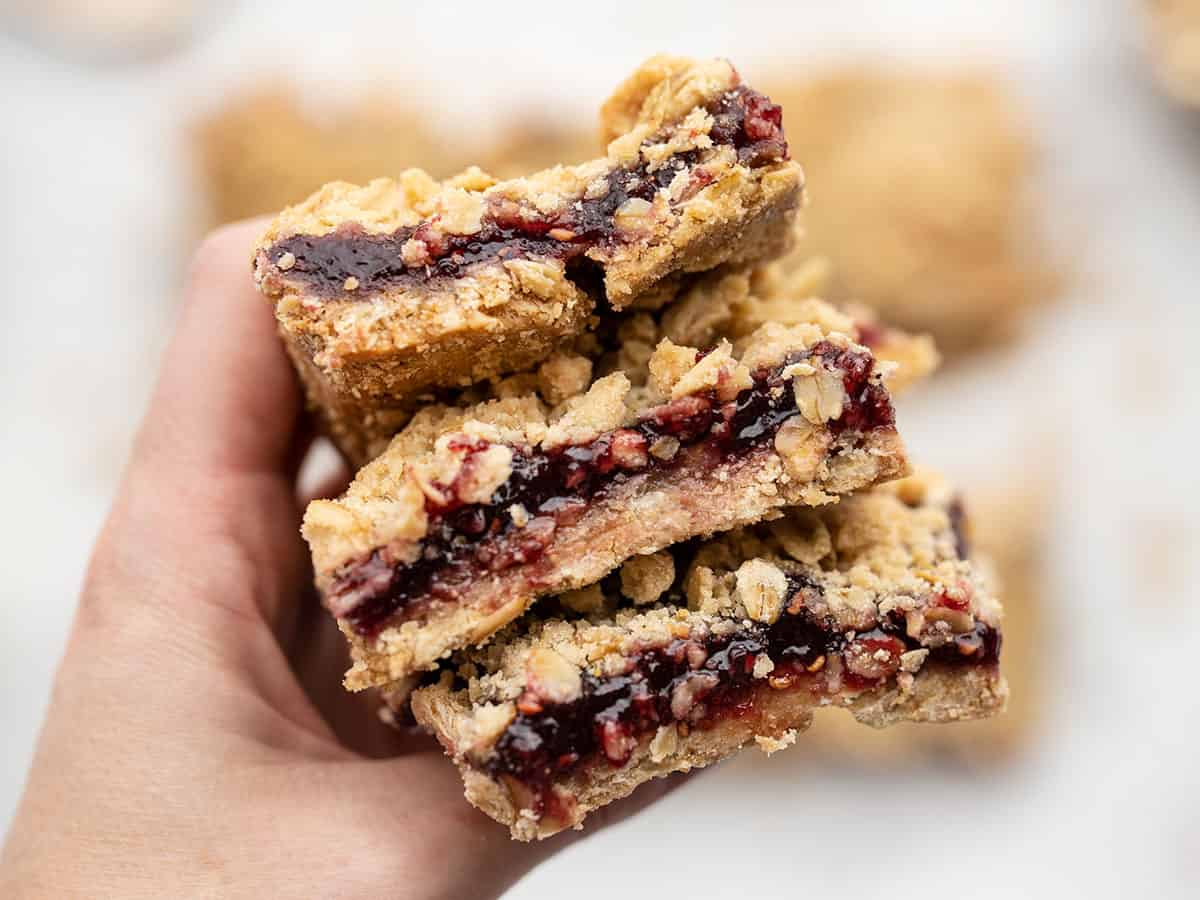 A hand holding a stack of raspberry oatmeal bars close to the camera
