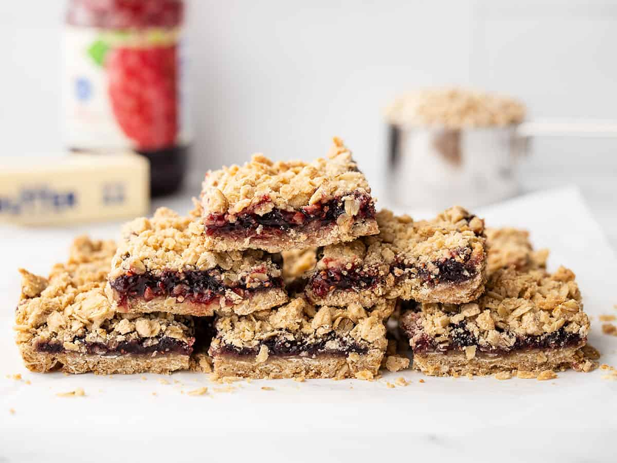 A pyramid of raspberry oatmeal bar squares with baking ingredients in the background