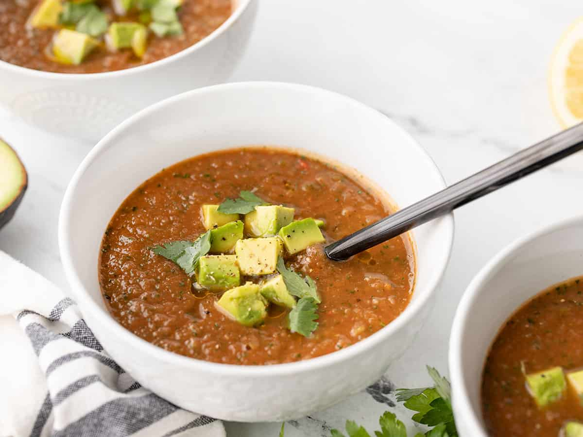 three bowls of gazpacho from the side, a spoon in one