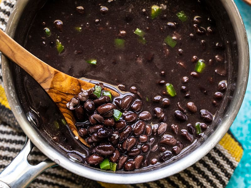 Close up of quick seasoned black beans in the sauce pot, being lifted by a wooden spoon.