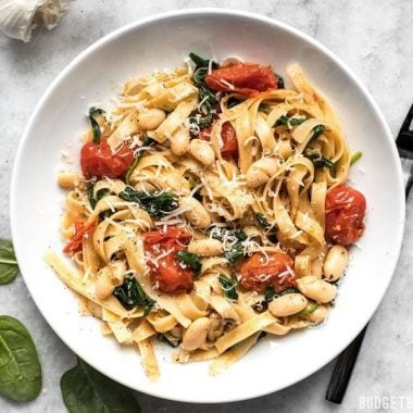This Tuscan White Bean Pasta is a fast and flavorful dish that is perfect for weeknight dinners. The caramelized garlic, basil, and Parmesan pack a huge flavor punch! BudgetBytes.com