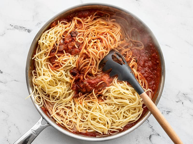 Add cooked spaghetti to puttanesca sauce in the skillet