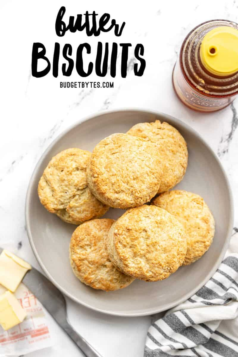 Homemade Butter Biscuits on a plate next to honey and butter