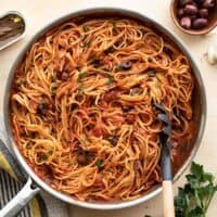 A skillet full of pasta puttanesca with anchovies and olives on the side