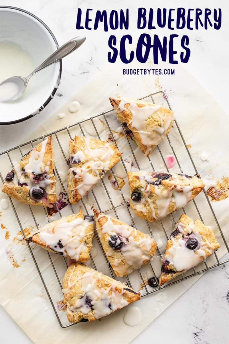 Lemon blueberry scones on a wire cooling rack with lemon glaze