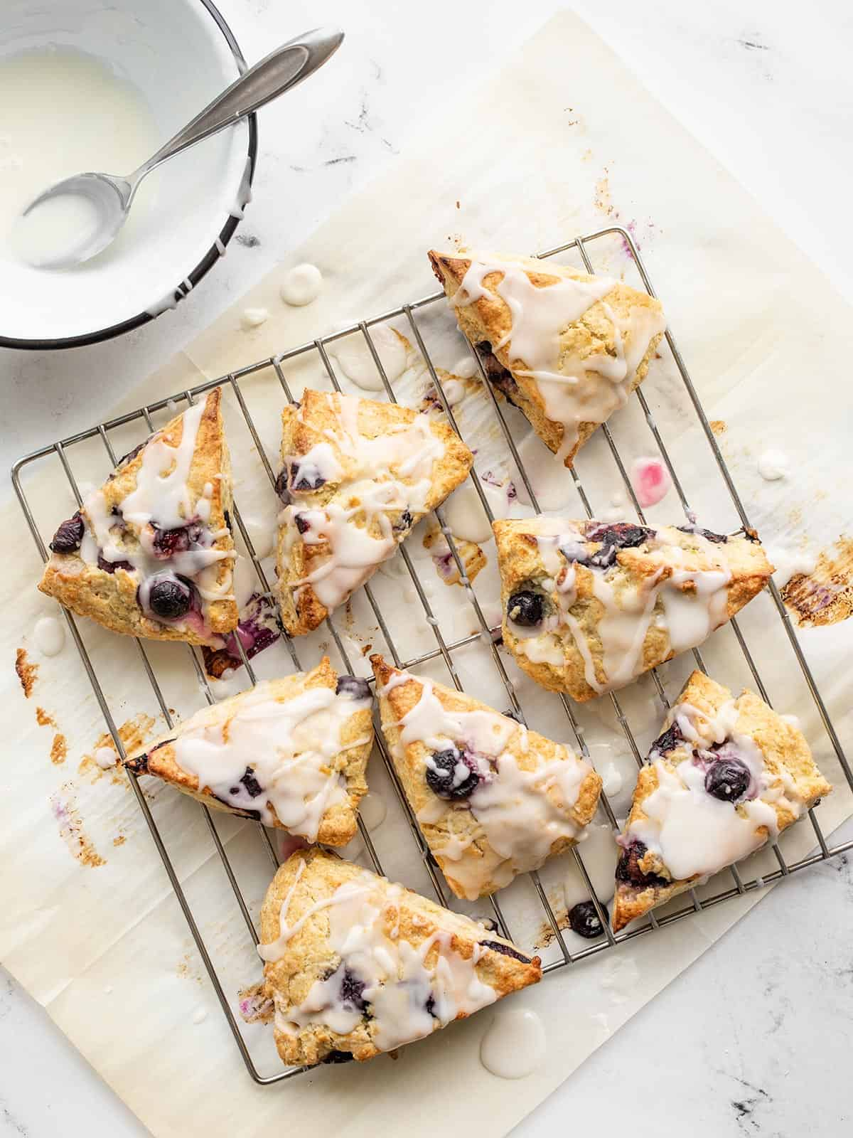 Lemon blueberry scones on a wire cooling rack drizzled with glaze