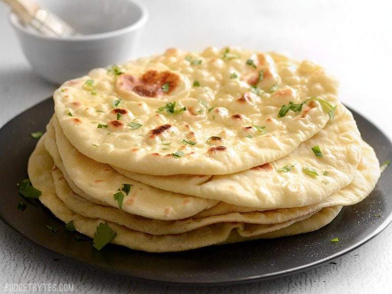 Soft, pillowy, homemade naan is easier to make than you think and it's great for sandwiches, pizza, dipping, and more. BudgetBytes.com