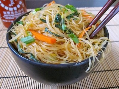 Singapore Noodles Singapore Noodles, Rice Vermicelli in black bowl with chop sticks and a bottle of Sriracha on the side