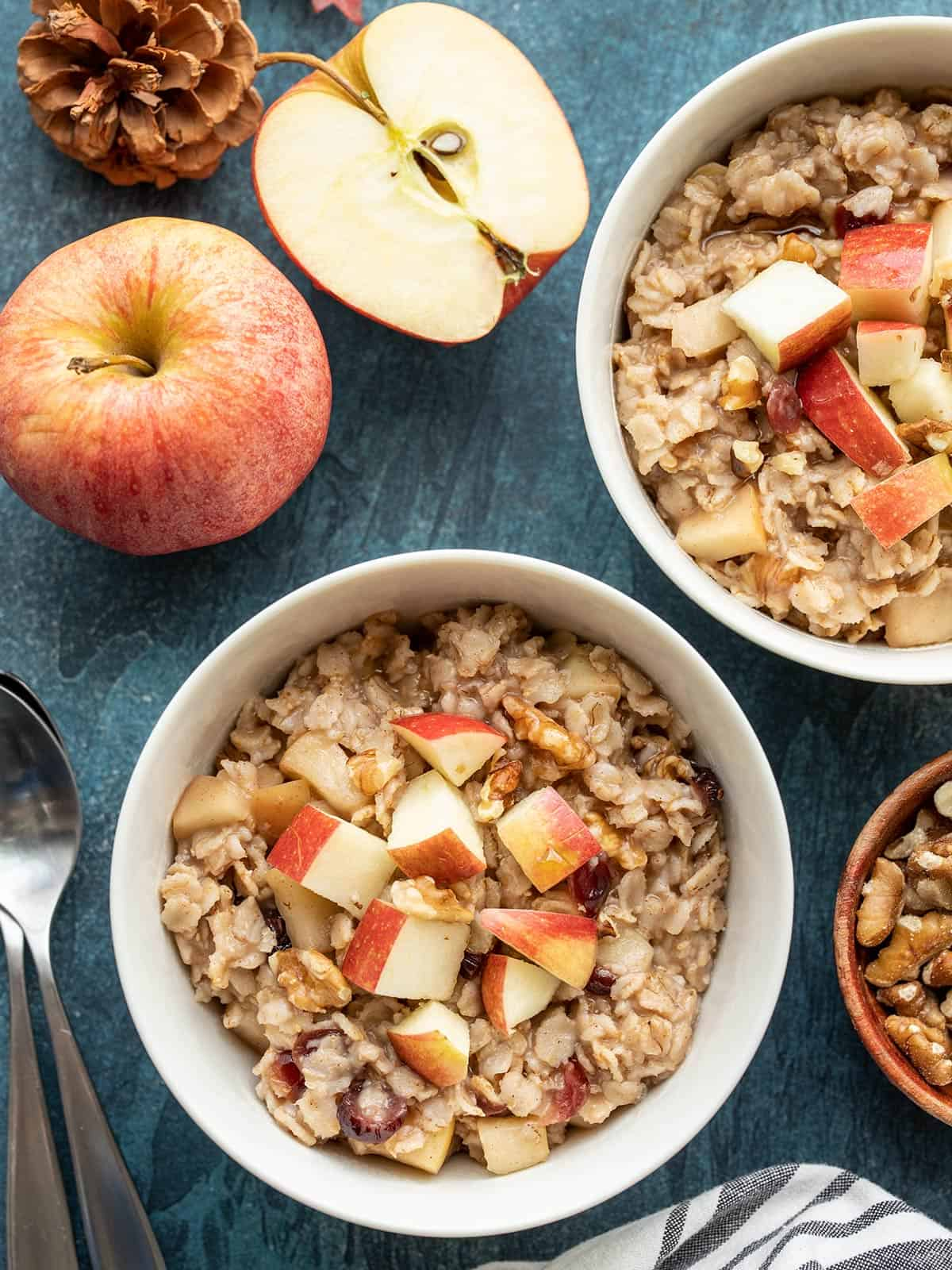 Overhead view of two bowls of autumn fruit and nut oatmeal