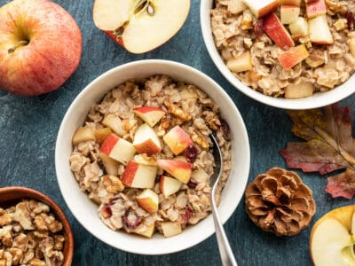Two bowls of autumn fruit and nut oatmeal surrounded by apples, leaves, and pinecones
