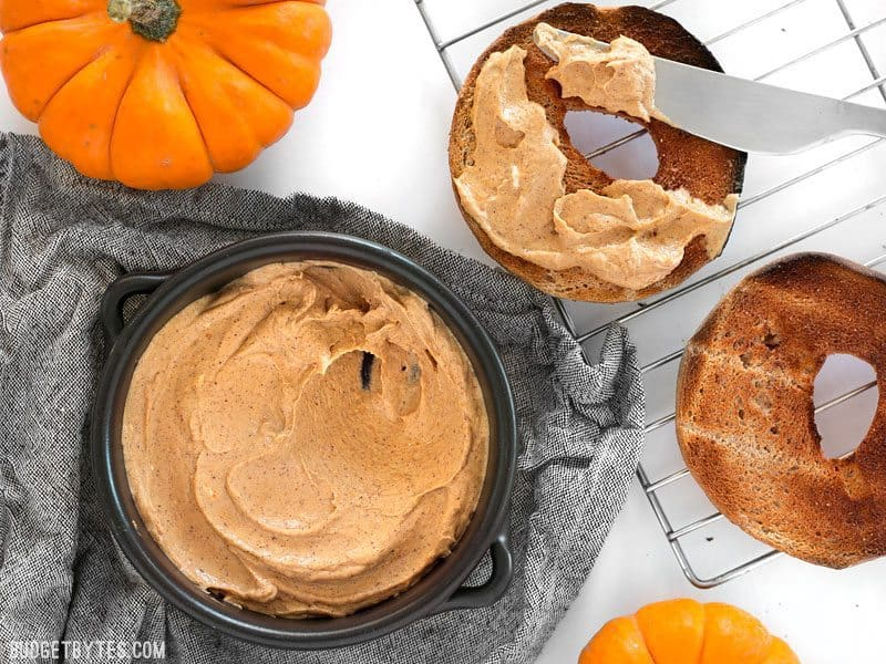 Pumpkin cream cheese spread in pan with bagel next to it being spread on