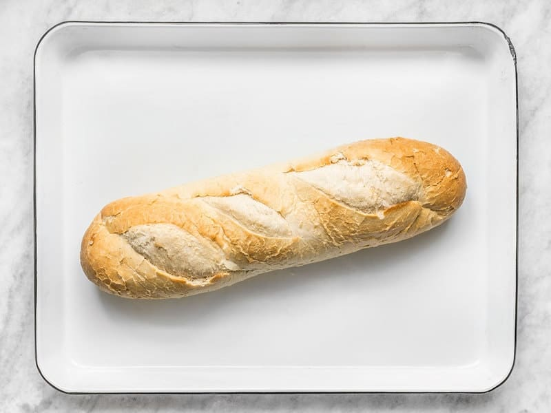 A loaf of French Bread on a white baking sheet