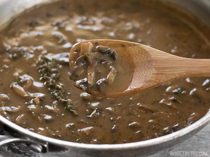 close up of gravy in pan with wooden spoon