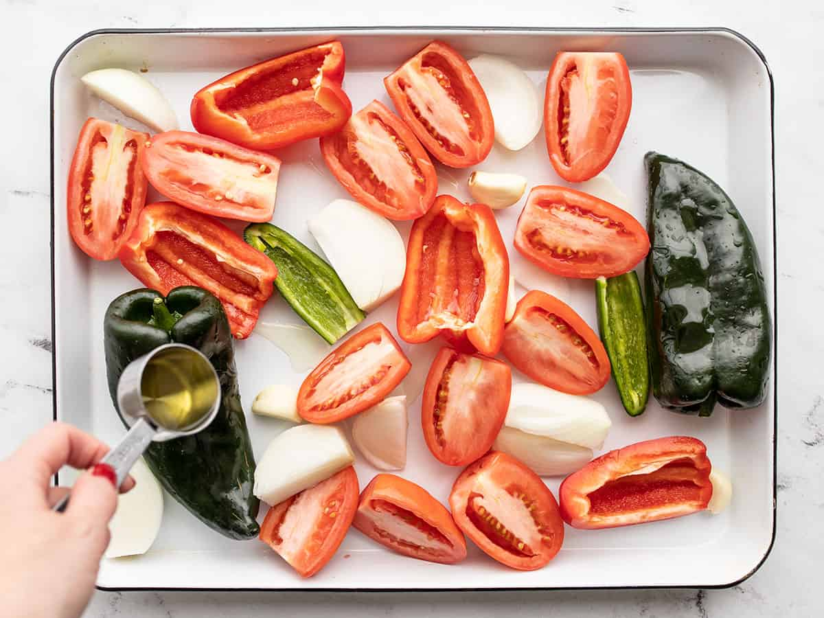 prepped vegetables on a baking sheet with oil being drizzled over top