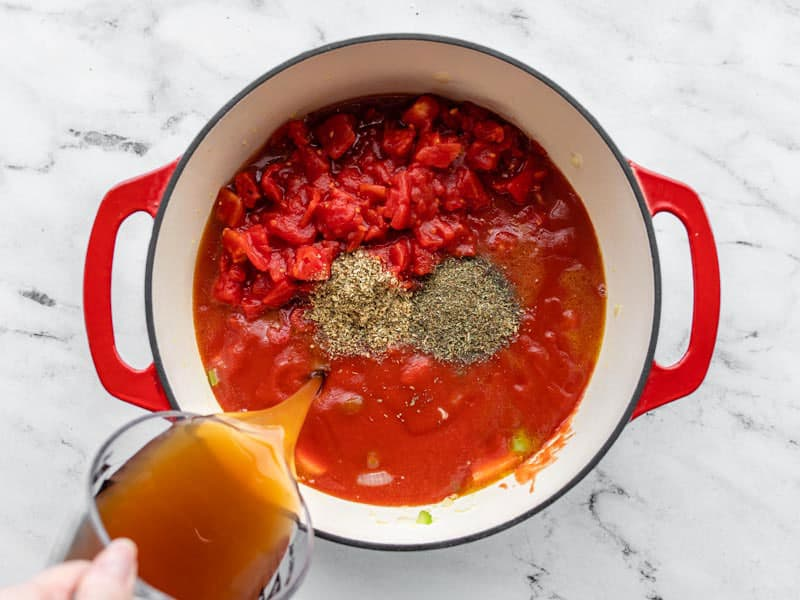Add tomatoes, herbs, and vegetable broth to soup pot