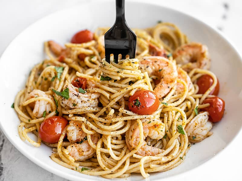 Front view of a bowl full of pesto shrimp pasta with a fork twirling the pasta in the center