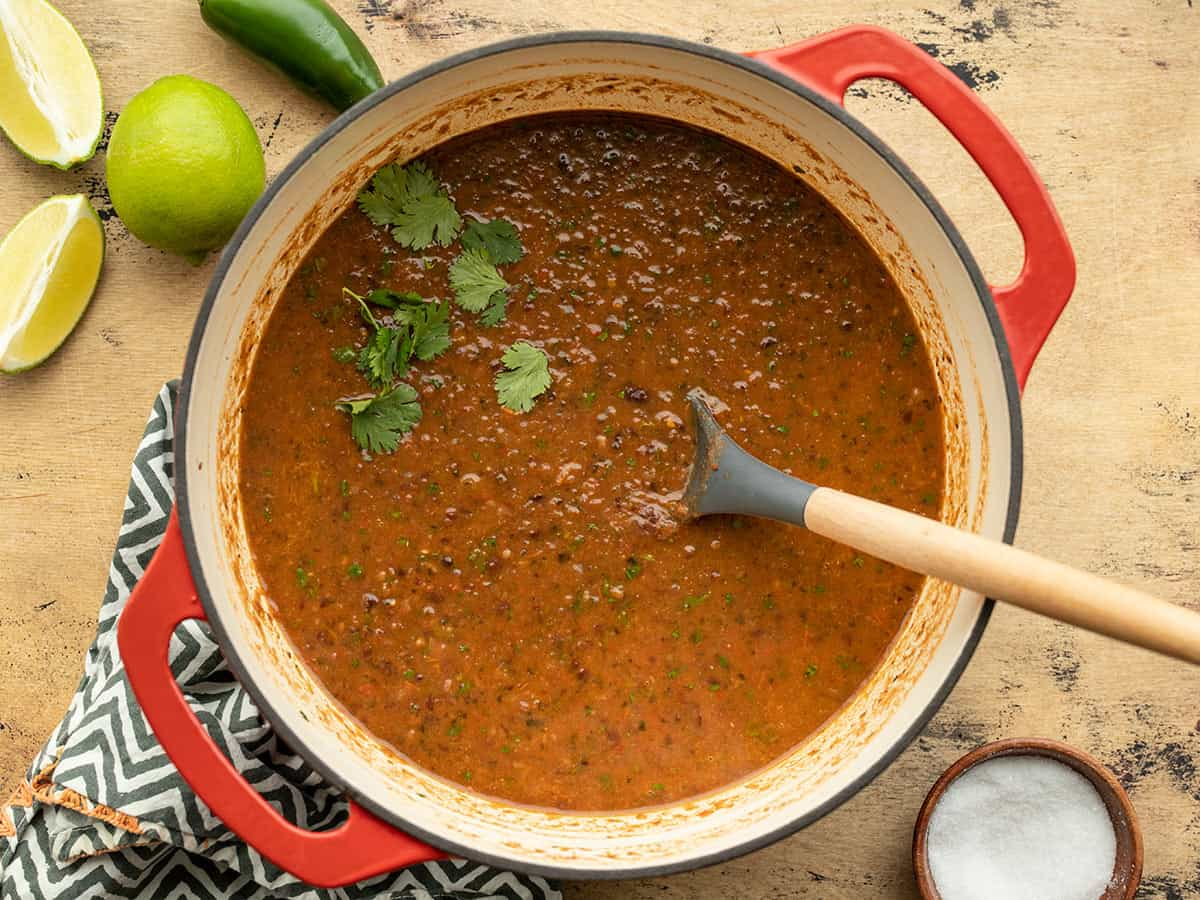 black bean and roasted salsa soup in a Dutch oven garnished with cilantro