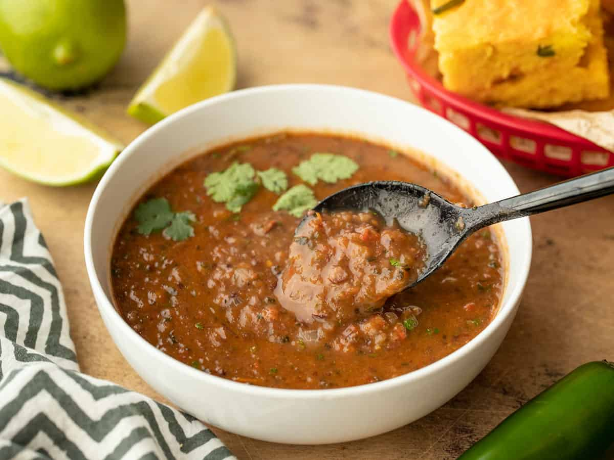 Side view of black bean and roasted salsa soup in a bowl with a spoon in the center