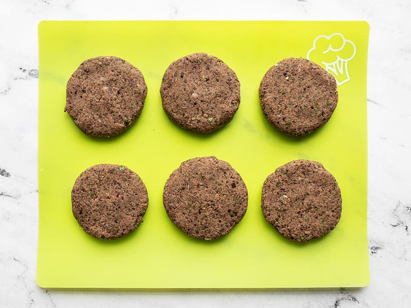 Shaped black bean burgers on a green cutting board