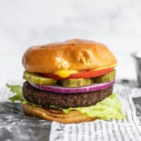 Side view of a single black bean burger on a bun, fully dressed, sitting on newsprint