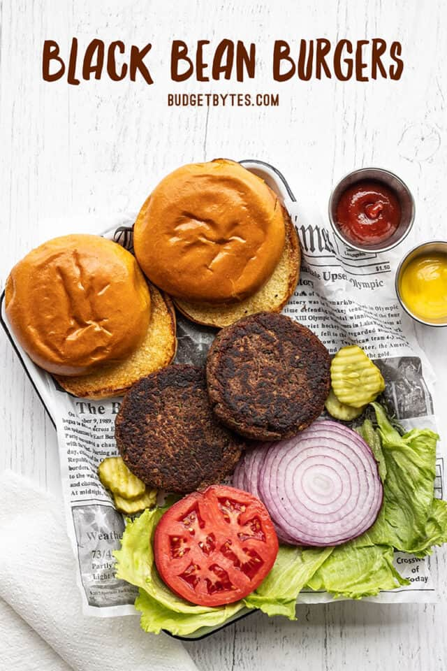 Two black bean burgers on a tray with buns and toppings. Title text at the top.
