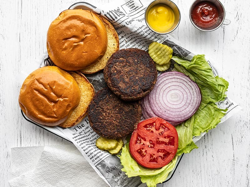 Black Bean burgers on a tray with buns, toppings, ketchup and mustard.