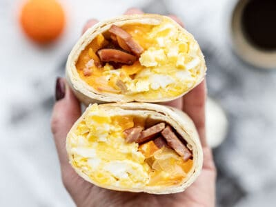 The open sides of a cut open breakfast burrito held toward the camera, close up.