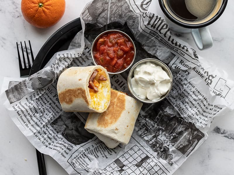 A reheated breakfast burrito on a plate with a newsprint liner, two small dishes of salsa and sour cream, a tangerine and cup of coffee on the side