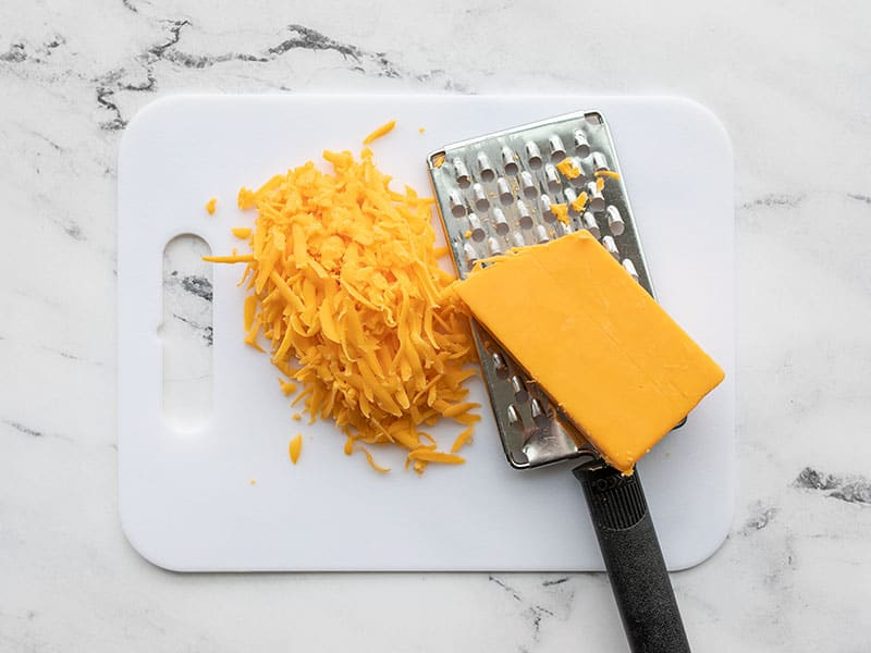 Shredded cheddar on a cutting board with the cheese grater.
