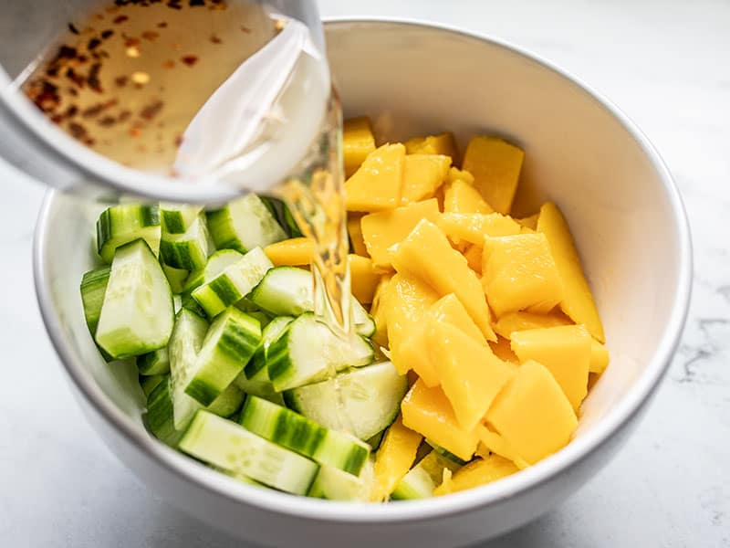 Dressing being poured over cucumber and mango in the bowl.