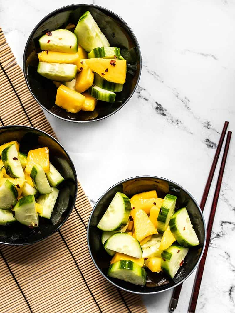 Three black ceramic bowls with Cucumber mango salad on a marble table with a bamboo mat and chopsticks.