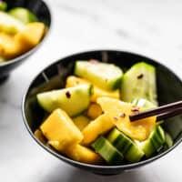Close up of a bowl of cucumber mango salad with chopsticks picking up a piece of mango