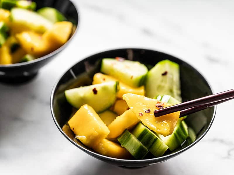 Close up of a bowl of cucumber mango salad with chopsticks picking up a piece of mango